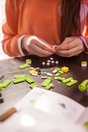 Girl building blocks of the green toy.