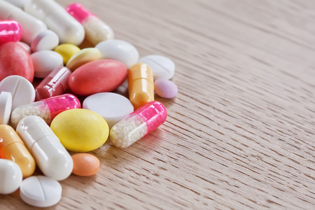 pilule: Multicoloured pills and capsules on the left part of wooden background
