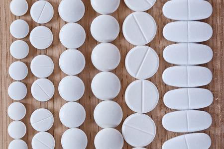 pilule: Diferentes p�ldoras blancas en el fondo de madera Foto de archivo