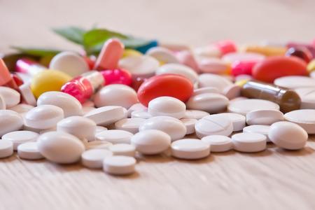 pilule: P�ldoras y c�psulas multicolores en el fondo de madera