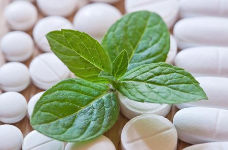 pilule: Diferentes p�ldoras blancas y follaje de menta sobre un fondo de madera.