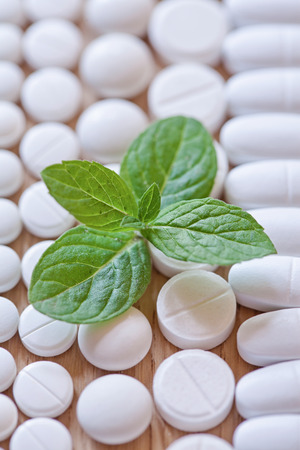 pilule: Different white pills and foliage mint on a wooden background.
