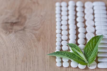 pilule: Diferentes p�ldoras blancas y follaje menta en un fondo de madera