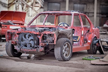 salvaging: Old rusty car without doors.