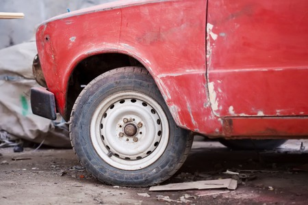 salvaging: Closeup photo of rusty red car wheel