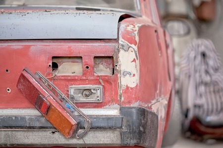 salvaging: Closeup photo backlight of red rusty car.