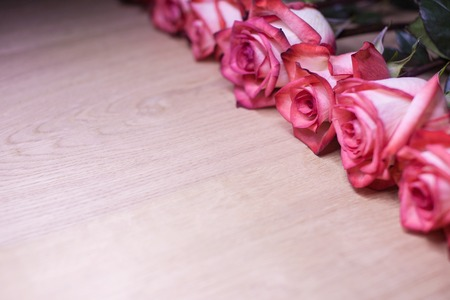 abreast: Several pink roses on a wooden background.