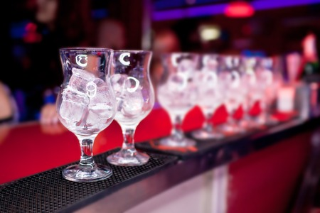 Glasses with ice on the bar counter at a nightclub