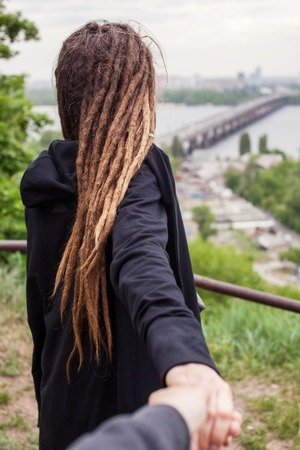 mano negra: The guy holding girl with dreadlocks in black hand on a background of Kyiv city.