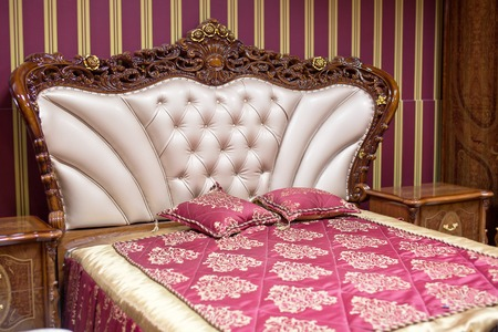 coverlet: Double bed with decorative headboard.