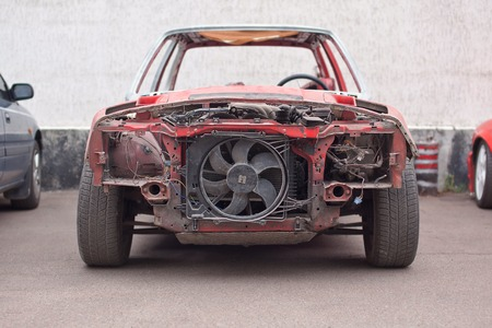 salvaging: Front view of red old rusty car. Stock Photo