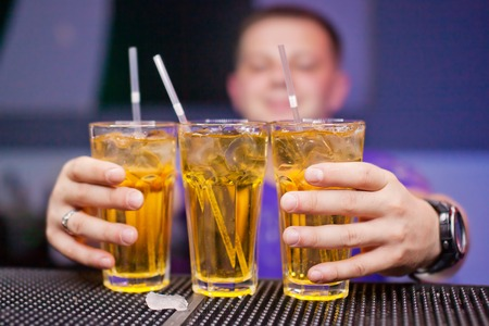 binge: Three glasses with a refreshing drink on bar counter.