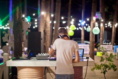 DJ at work in outdoor cafe, night photo. Stock Photo