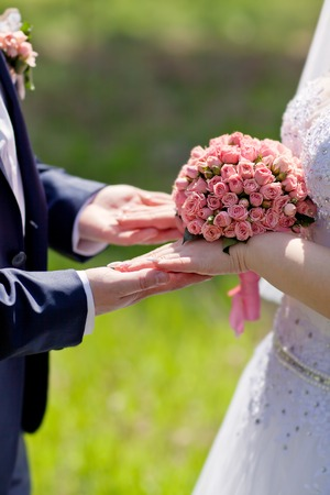 twain: Hands of bride and groom holding a bouquet of pink roses.