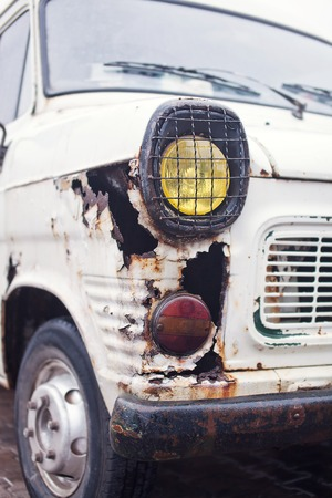 salvaging: Close-up photo of rusty wing white truck.