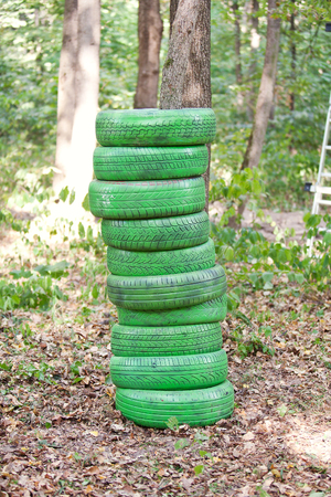 utilized: Stack of old green tires in the forest.