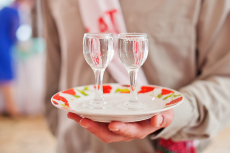 matchmaker: Two glasses of vodka on a plate in hand Stock Photo
