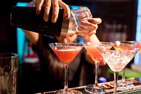 tomando alcohol: El camarero chica se prepara un cóctel en la discoteca.