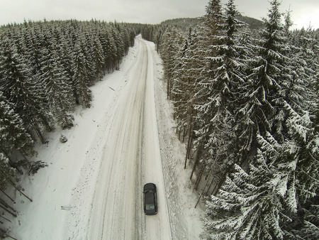 snowcovered: Aerial shot of snow-covered road in the countryside Carpathian Mountains with car on way. Stock Photo