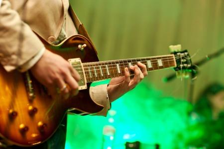 gitara: Muzyk gra na gitarze w szarym płaszczu. Zdjęcie Seryjne