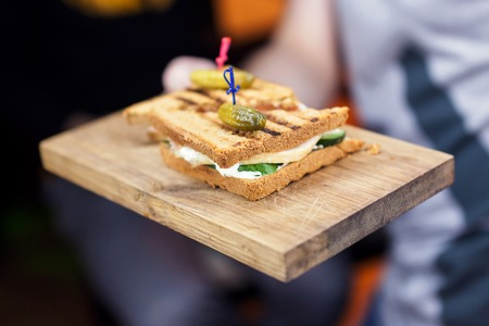 cuke: Fresh and tasty sandwich with ham and vegetables on wooden board. Stock Photo
