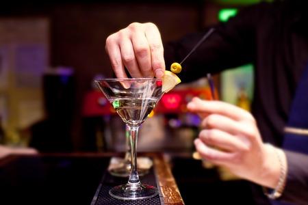 The bartender decorates stemware with martini.