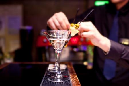 stemware: The bartender decorates stemware with martini.