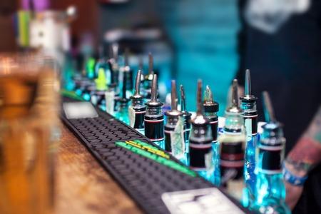 bebidas alcohÓlicas: Muchas botellas con bebidas alcohólicas en la barra del bar.