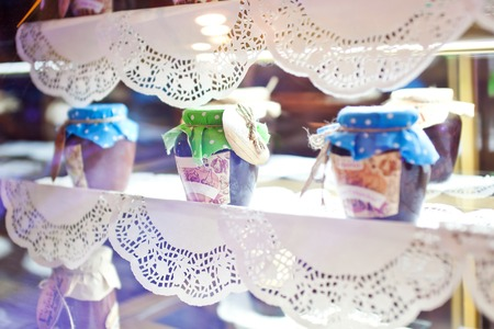 Jars with jam on a decorated openwork napkins showcase. Stock Photo