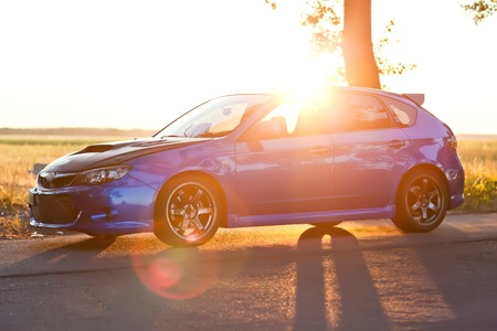 Left side view of blue sport car with sun light.
