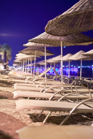 sunbeds: Sunbeds and umbrellas on the beach in the evening. Stock Photo