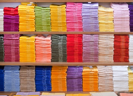 terrycloth: Stacks of colored terry towels on the shelves in a shop. Stock Photo