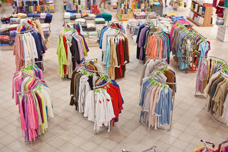 bathrobes: Shop home textiles with hangers which hang colored bathrobes. Stock Photo
