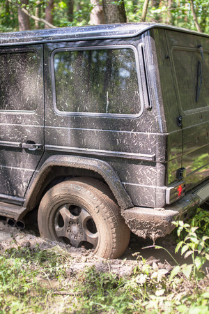 SUV got stuck in the mud in the forest, off-road.