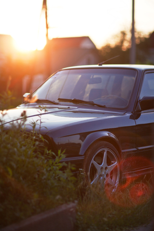 front side: Front side of black old car with beatifull sunset. Stock Photo