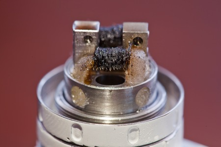 Macro photo of dirty twisted coil mounted in the electronic cigarette. Stock Photo