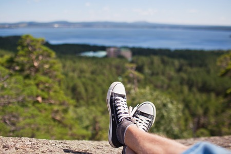 Legs in black shoes on a rock in the mountains.