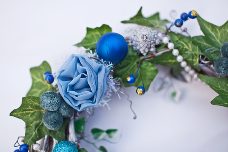 Christmas decorative wreath with ivy leaves, fir-tree balls and artificial flowers. Fragment Stock Photo