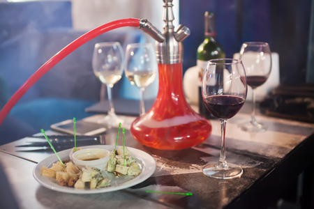 smolder: Red hookah on table with vine and cheese