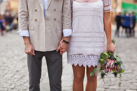 mixed marriage: A guy holding a girl by the hand with a bouquet of flowers.