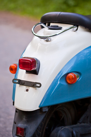 Rear wing and headlight of blue retro scooter