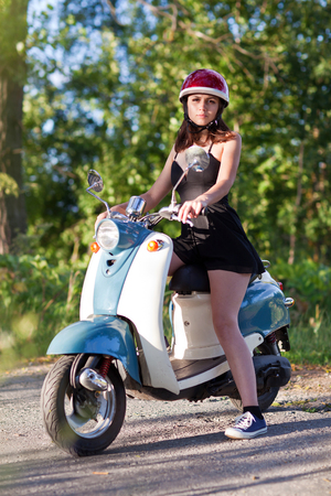 A girl with a scooter on a country road.