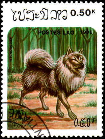 LAOS - CIRCA 1986: postage stamp, printed in Laos, shows Keeshond dog Editorial