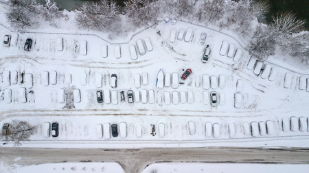 Aerila view of snow-covered cars stand in the parking lot on a winter day Stock Photo