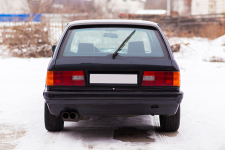 Old, black, German family car rear view in winter Stock Photo