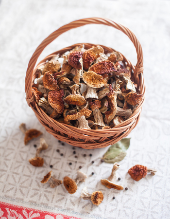 Dried white mushrooms in a beautiful wicker basket on the table Stock Photo
