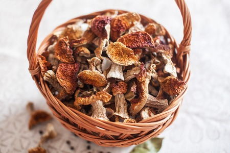 Dried white mushrooms in a beautiful wicker basket on the table. 写真素材