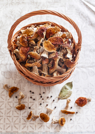 Dried white mushrooms in a beautiful wicker basket on the table. Stock Photo