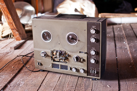 Old tape recorder on a wooden floor.