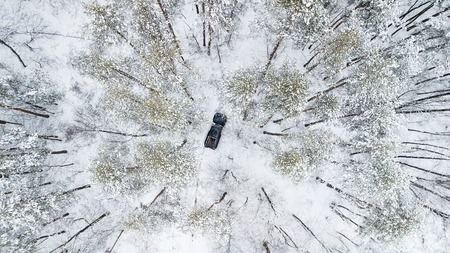 Aerial view on SUV 6x6 that rides by winter road in snow-covered forest.